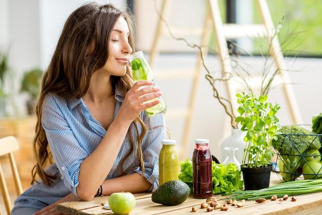 家で飲み物と健康的な緑の食べ物と一緒に座っている美しい女性。ビーガンミールとデトックスのコンセプト
