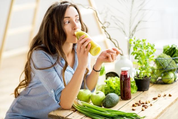 健康的な緑の食べ物と一緒に座って、家でスムージーを飲む美しい女性。ビーガンミールとデトックスのコンセプト