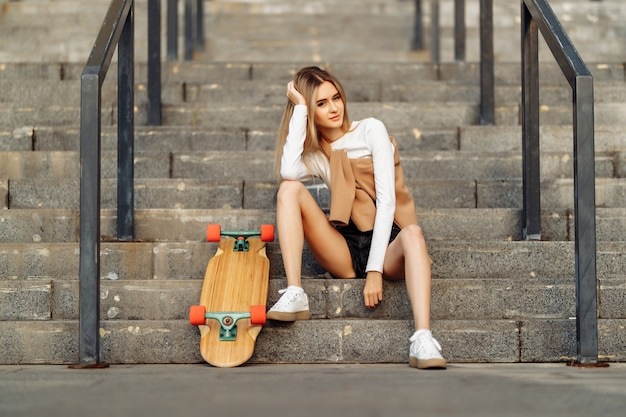 美しい女性が街中をスケートします。ライフスタイルと夏休み。高品質の写真