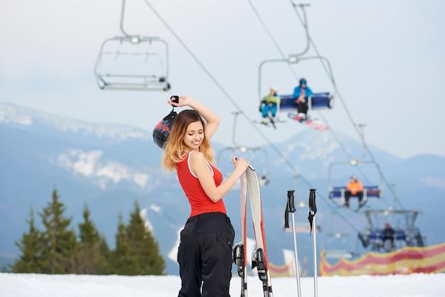 冬のスキーリゾートでスキー用具と立っている美しい女性スキーヤー。スキーリフトと山。スキーシーズンとウィンタースポーツのコンセプト