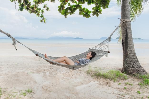 Красивая женщина спит на гамаке на пляже, момент от призвания.