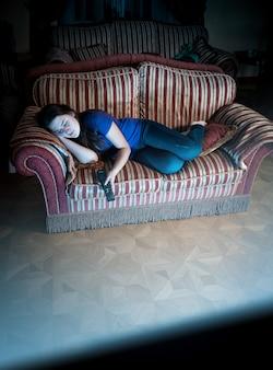 Красивая женщина спит на диване во время просмотра телевизора
