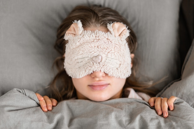 A beautiful woman sleeps in bed at home in a sleep mask on her face and sees good dreams. good morning. healthy sleep.