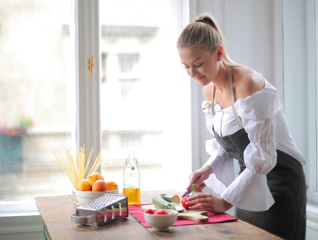 美しい女性が台所で野菜をスライス