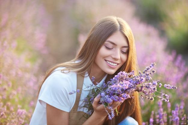 ラベンダー畑で花束の香りを嗅ぐ美女