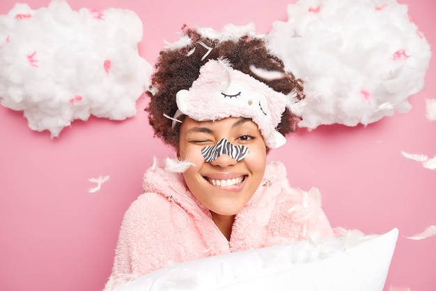 Beautiful woman smiles broadly bites lips applies white strip nose mask for cleansing blackheads wants to have healthy clean skin wears blindfold and pajama holds soft pillow