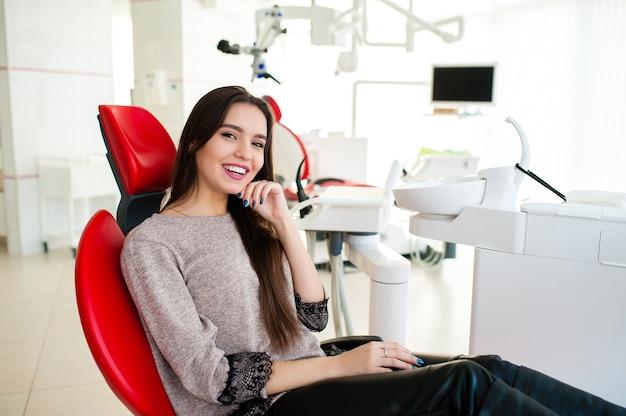 Красивая женщина улыбается в стоматологическом кресле