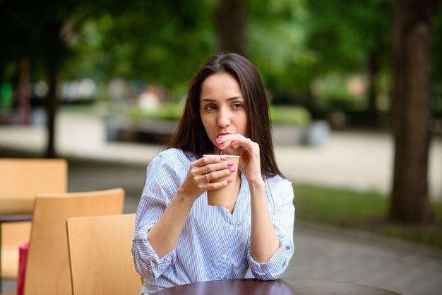 Красивая женщина, улыбаясь и пить кофе.