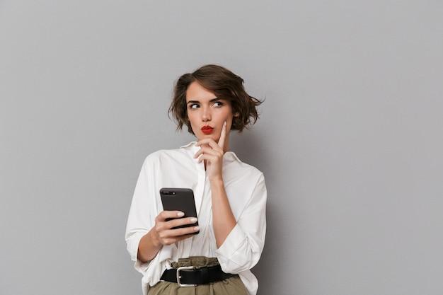 灰色の壁に隔離、笑顔で携帯電話を保持している美しい女性