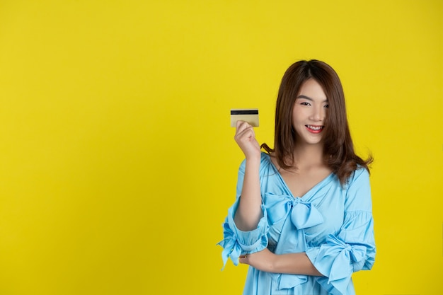 Beautiful woman smiling at camera and holding credit card on yellow wall