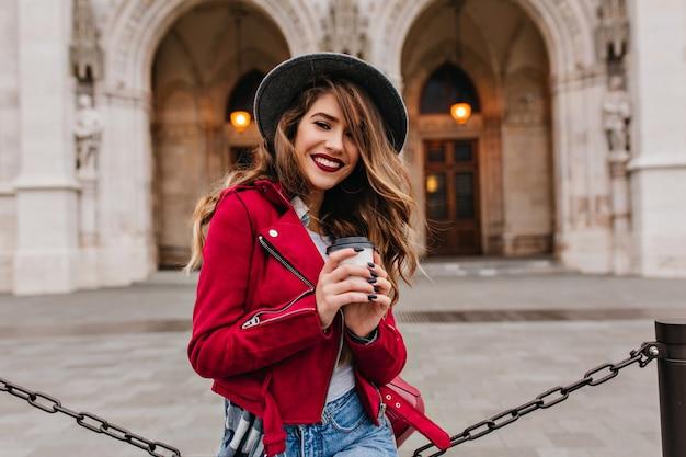 Bella donna che sorride alla macchina fotografica mentre beve latte accanto al museo