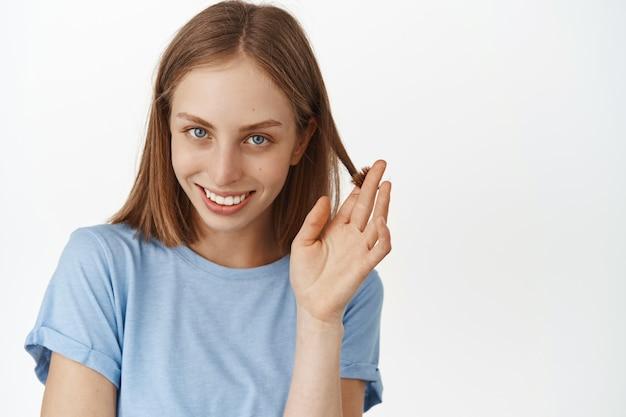 コケティッシュに笑って、髪の毛で遊んで、正面で幸せでかわいいを見つめ、いちゃつく、白い壁にtシャツを着て立っている美しい女性。