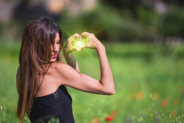 Beautiful woman smiling. heart symbol shaped with green flare inside. love, nature concept