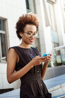 Beautiful woman smiling looking at phone walking down city