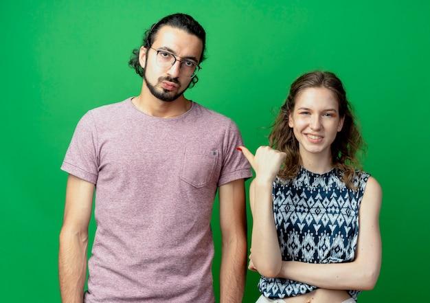 Bella donna sorridente che punta al suo fidanzato scontento, giovane coppia uomo e donna oltre il muro verde
