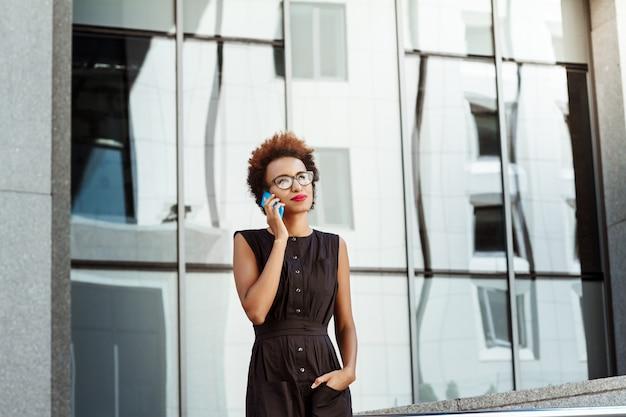Beautiful woman smiling speaking on phone walking down city