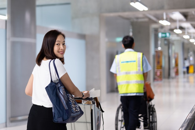 Beautiful woman smiling on vacation with luggage trolley in airport building.