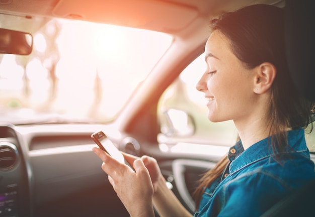 Beautiful woman smiling while sitting on the front passenger seats in the car. girl is using a smartphone