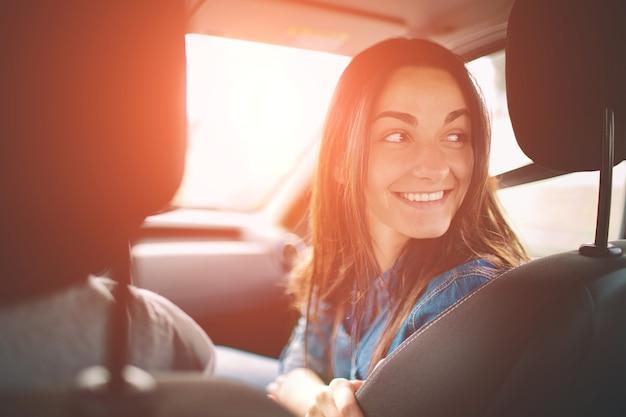 차에 앞 좌석에 앉아있는 동안 웃는 아름다운 여자