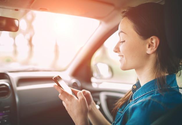 Красивая женщина, улыбаясь, сидя на сиденьях переднего пассажира в машине. девушка использует смартфон