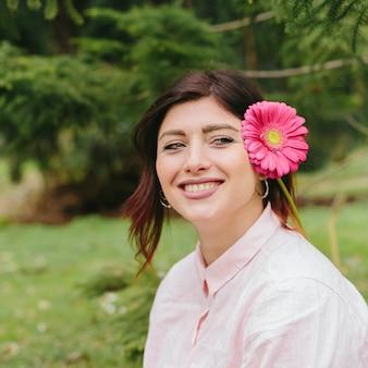 Bella donna sorridente con un fiore nei capelli