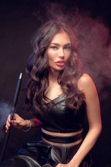 Beautiful woman in smokes hookah or shisha.