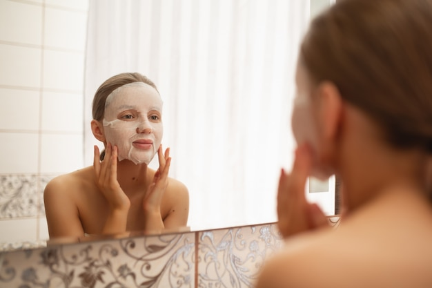 A beautiful woman smoothes, puts on a face a cosmetic mask in the bathroom by the mirror
