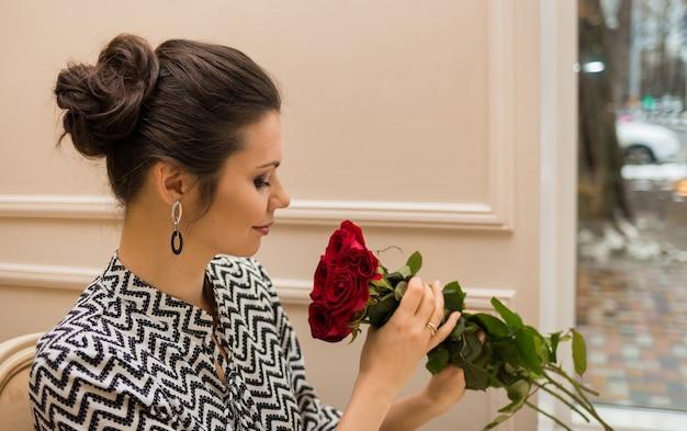 美しい女性がカフェでバラの花束を嗅ぐ
