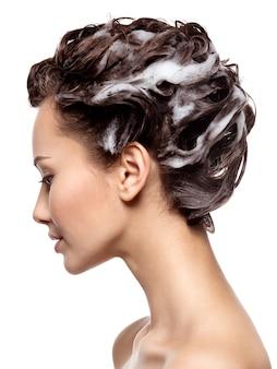 茶色の髪を石鹸で洗う美しい女性-白い壁に