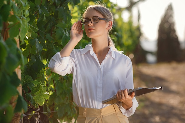 Beautiful woman sommelier checks grapes before harvest. biological concept id , organic food and fine wine handmade