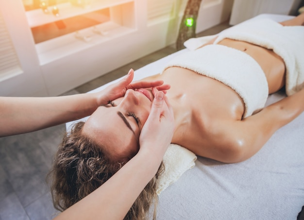 Beautiful woman in spa salon getting facial massage