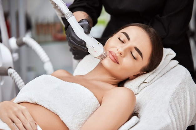 Beautiful woman in spa salon receiving laser depilation theraphy for her chin, female customer of beauty clinic of facial hair removal