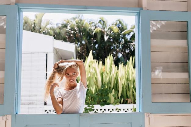 Красивая женщина тратить солнечный день напольный. фото красивой девушки-модели со светлыми волосами, позирующей с застенчивой улыбкой