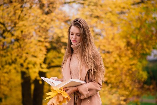 Красивая женщина проводит время в парке в осенний сезон
