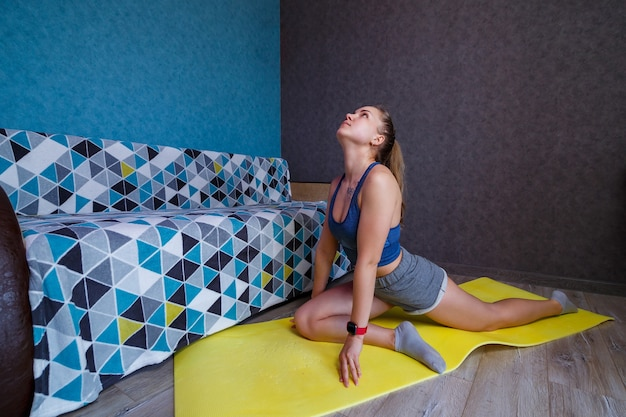 Beautiful woman in sportswear, shorts and a bra standing in a pose, exercises, attractive girl practicing yoga, working out at home or in a modern yoga studio, body stretching