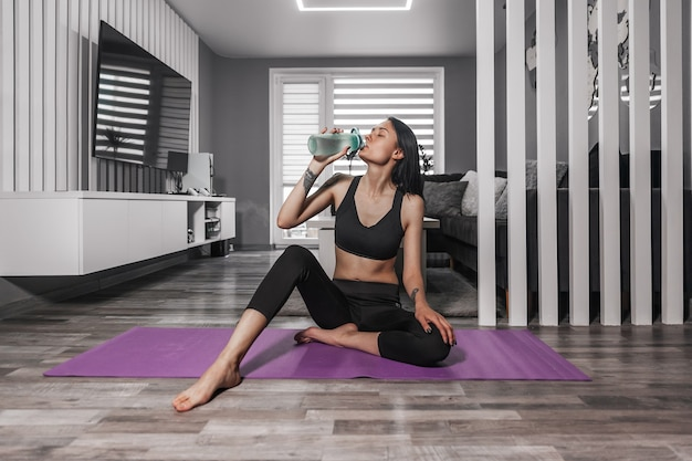 Beautiful woman in sportswear sits on a yoga mat and drinks water