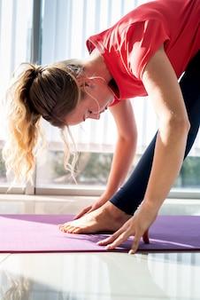 Beautiful woman in sportswear sitting in mat practicing yoga, meditation indoors
