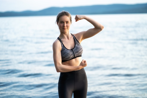 A beautiful woman in sportswear stands in the lake, illuminated by the rays of the sunset and shows her pumped up arms