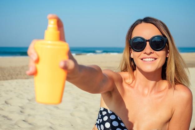Beautiful woman sprinkles a sun spray on the beach