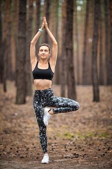 Красивая женщина стоя и занимаясь йогой в лесу. концепция упражнений и медитации. оплатите почтение или поднимите руку концепции. сосновый лес в летней тематике. вид сзади.