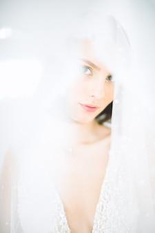 Красивая женщина стоя и смотря в комнате с белизной в длинном белом платье.