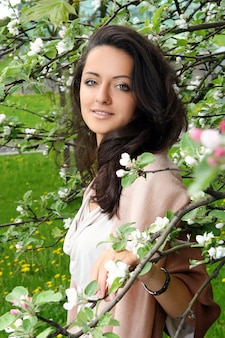 Beautiful woman standing by blossoming tree