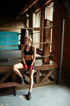 Красивая женщина, стоя у боксерского ринга