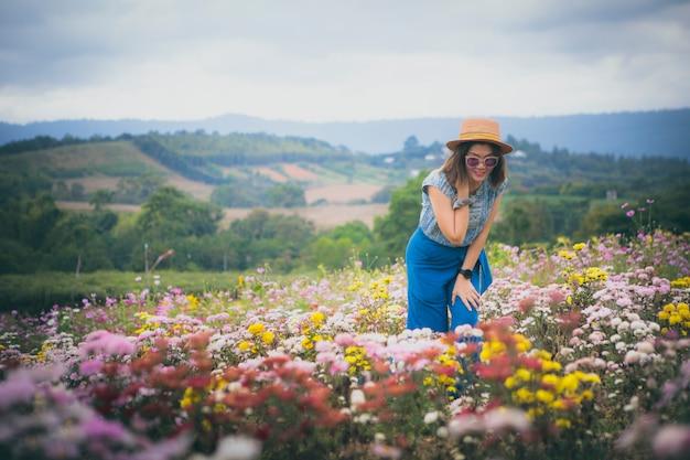咲く花畑に立っている美しい女性