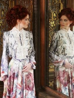 거울 궁전 방에 서있는 아름 다운 여자.