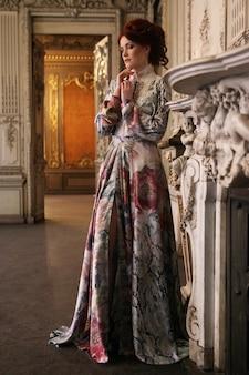 궁전 방에 서있는 아름 다운 여자.