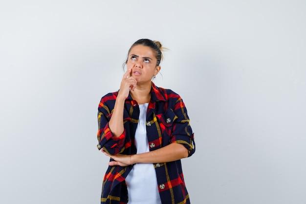 思考ポーズで立っている美しい女性、白いtシャツ、頬のシャツの頬に人差し指を置き、物思いにふける。正面図。