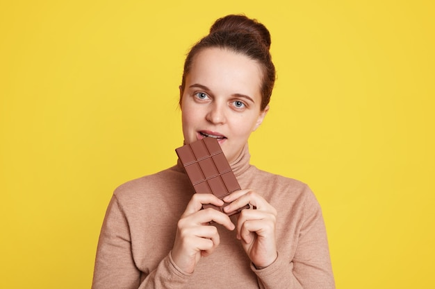 Beautiful woman standing isolated over yellow wall and biting bar of chocolate, feels hungry, wearing casual beige sweater, having dark hair and hair bun.