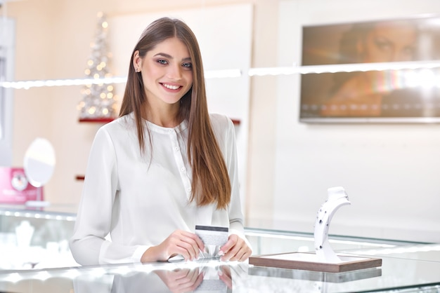 Beautiful woman standing near the counter of a jewelry store ready to pay for the necklace