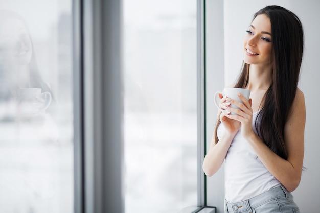 窓の近くに立っている美しい女性